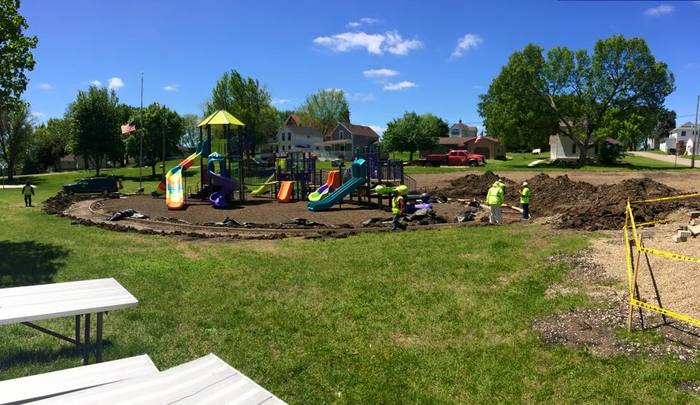 WORKING ON THE SIDEWALK AROUND THE PLAYGROUND EQUIPMENT